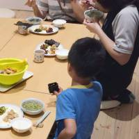 Children eat dinner with officials at an after-school care center in Toda, Saitama Prefecture, in this undated photo. | COURTESY OF LEARNING FOR ALL / VIA KYODO