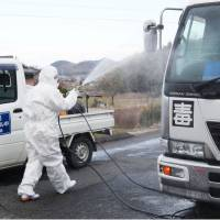 A man sprays antiseptic solution on a truck Thursday near a poultry farm where bird flu is suspected to have infected chickens, in Sanuki, Kagawa Prefecture. | KYODO