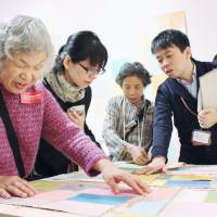 A curator (right) explains an artwork while a woman touches it, at an event held at Mori Art Museum in Tokyo's Roppongi district in October to help visually impaired people appreciate art. | KYODO