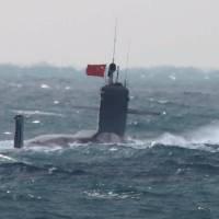 A submarine is seen cruising in the high seas northwest of the Senkaku Islands Friday hoisting a Chinese flag. | DEFENSE MINISTRY / VIA KYODO