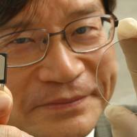 Professor of Engineering Hiroshi Amano holds a power semiconductor (left) and a wafer of crystallized gallium nitride at Nagoya University. His team is working on developing a wireless power supply system using crystallized gallium nitride technology. | CHUNICHI SHIMBUN