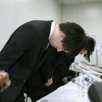 Coincheck Inc. CEO Koichiro Wada (left) bows in apology Friday in Tokyo after ¥58 billion was reportedly stolen from the cryptocurrency exchange. | KYODO