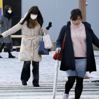 Pedestrians cross an icy road in Nagoya on Thursday morning. Strong winds and heavy snow have hit wide areas of the country. | KYODO