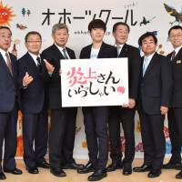 Daisuke Muramoto (center) poses with heads of municipalities from near the Sea of Okhotsk in Hokkaido at a Tokyo event to promote the region in December. Known for cold weather, the municipalities vowed to 'cool' the 'flame of controversy' created by the sharp-tongued comedian. | KYODO