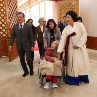 South Korean President Moon Jae-in and first lady Kim Jung-suk greet a former 'comfort woman' at the Presidential Blue House in Seoul on Jan. 4. | REUTERS