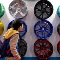 A young boy walks in front of wheel rims on display at the Tokyo Auto Salon at Makuhari Messe in Chiba on Friday.   AFP-JIJI
