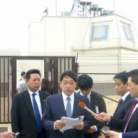 Defense Minister Itsunori Onodera (center) answers questions from reporters in Kauai, Hawaii, on Wednesday after inspecting a test complex for the Aegis Ashore missile defense system.   KYODO
