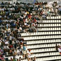 People avoid the sun during the Olympic Games at a stadium in Athens in August 2004.   REUTERS / VIA KYODO