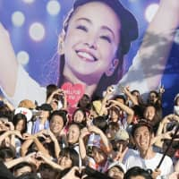 Fans of pop star Namie Amuro gather in front of one of her posters after her final concert in Ginowan, Okinawa Prefecture, in September. | KYODO