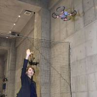 Mei Watanabe, head of Drone Museum Horie in the city of Osaka, controls a drone with hand gestures on Dec. 15. | KYODO