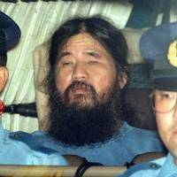 Aum Shinrikyo guru Shoko Asahara, whose real name is Chizuo Matsumoto, is escorted by police officers in September 1995. | KYODO