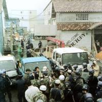 Police officers squeeze between a barricade of cars to investigate Aum Shinrikyo's facility in the village of Kamikuishiki, Yamanashi Prefecture, in April 1995. | KYODO