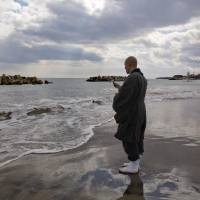 A Buddhist priest prays on a beach in Minamisoma, Fukushima Prefecture, in March 2017. The area was hit hard by the 2011 earthquake, tsunami and nuclear disaster. | KYODO