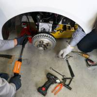 Employees install the suspension on a prototype of Fomm Corp.'s Concept One electric vehicle at the company's workshop in Kawasaki on Dec. 4. | BLOOMBERG