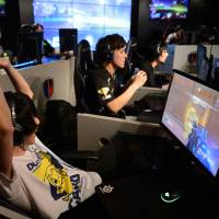 Gamers participate in the AOC Open esports event in Tokyo last July. | BLOOMBERG