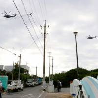 U.S. choppers fly near Futenma No. 2 Elementary School in Ginowan, Okinawa Prefecture, on Thursday. The school conducted an evacuation drill the same day against U.S. helicopters after a window from one landed on its grounds on Dec. 13, nearly hitting children. | KYODO