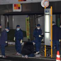 Police investigate a scene where multiple stabbings took place in the city of Hiroshima. A 33-year-old man was arrested early Monday on suspicion of attacking two men on a street, killing one of them. | KYODO