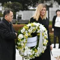 Beatrice Fihn, executive director of the International Campaign to Abolish Nuclear Weapons, and Akira Kawasaki, a member of the group's international steering committee, place a wreath at the Cenotaph for A-bomb Victims in Hiroshima on Monday. | KYODO