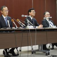 Kyoto University professor Shinya Yamanaka (left)and other officials apologize at a news conference in Kyoto on Monday. | KYODO