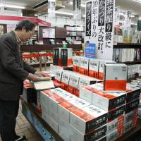 A man looks at the newest edition of the Kojien dictionary at a bookstore in Tokyo's Chiyoda Ward on Jan. 12.   KYODO