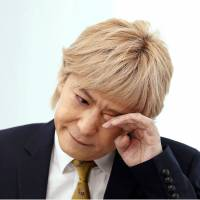 Famed music producer Tetsuya Komuro wipes away tears during a Friday news conference in Tokyo as he announces his retirement from the music industry. | KYODO