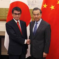 Foreign Minister Taro Kono (left) and his Chinese counterpart, Wang Yi, pose for photos before their meeting at the Diaoyutai State Guesthouse in Beijing on Sunday. | AP