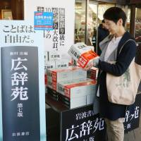 A woman looks at the new edition of Kojien dictionary at a bookstore in Tokyo's Chiyoda Ward on Friday.   KYODO