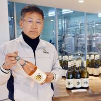 Hiroshi Matsuzaka, president of Enzan Factory Co. in Kofu, Yamanashi Prefecture, holds a bottle of wine produced at his semiconductor plant-turned-winery. | KYODO