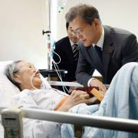 S. Korean President Moon Jae-in is seen with former 'comfort woman' Kim Bok-dong at a hospital in Seoul on Thursday in this government released photo.   REUTERS