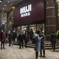 Shoppers walk past a Muji store, operated by Ryohin Keikaku Co., in Shanghai in December 2015. | BLOOMBERG