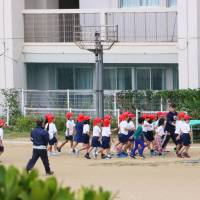 Elementary school students take part in an evacuation drill on Thursday in Ginowan, Okinawa Prefecture, as a precaution when U.S. military helicopters approach, after a window from a similar U.S. aircraft fell on the school grounds in December. | KYODO