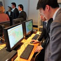 A visitor to the University of Tokyo Open Data Center in Bunkyo Ward on Jan. 18 looks at a map created from open data provided by a municipal government. | SHUSUKE MURAI