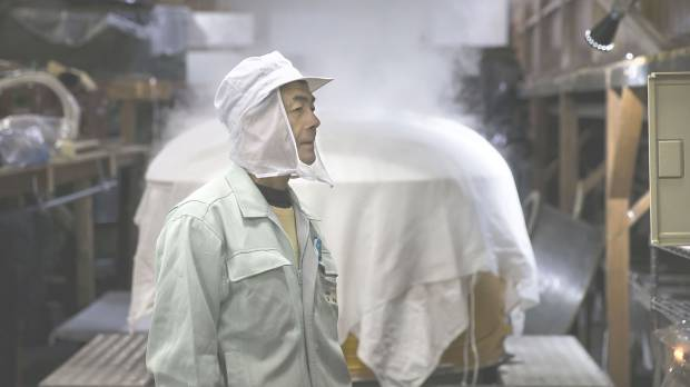 An employee stands in front of a rice steamer at a Suehiro Sake Co. brewery in Aizuwakamatsu, Fukushima Prefecture, on Nov. 30.