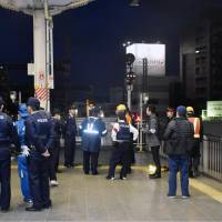 Police and railway staff gather Saturday on a train platform at Okayama Station in the city after a boy was found walking on the tracks of the Sanyo Shinkansen Line. | KYODO