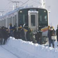 Passengers on Friday walk out of a train on East Japan Railway Co.'s Shinetsu Line, where they spent the night after being stranded between stations by heavy snowfall the night before in Sanjo, Niigata Prefecture. | KYODO