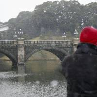 Snow falls near the Imperial Palace in Tokyo's Chiyoda Ward on Monday. | KYODO