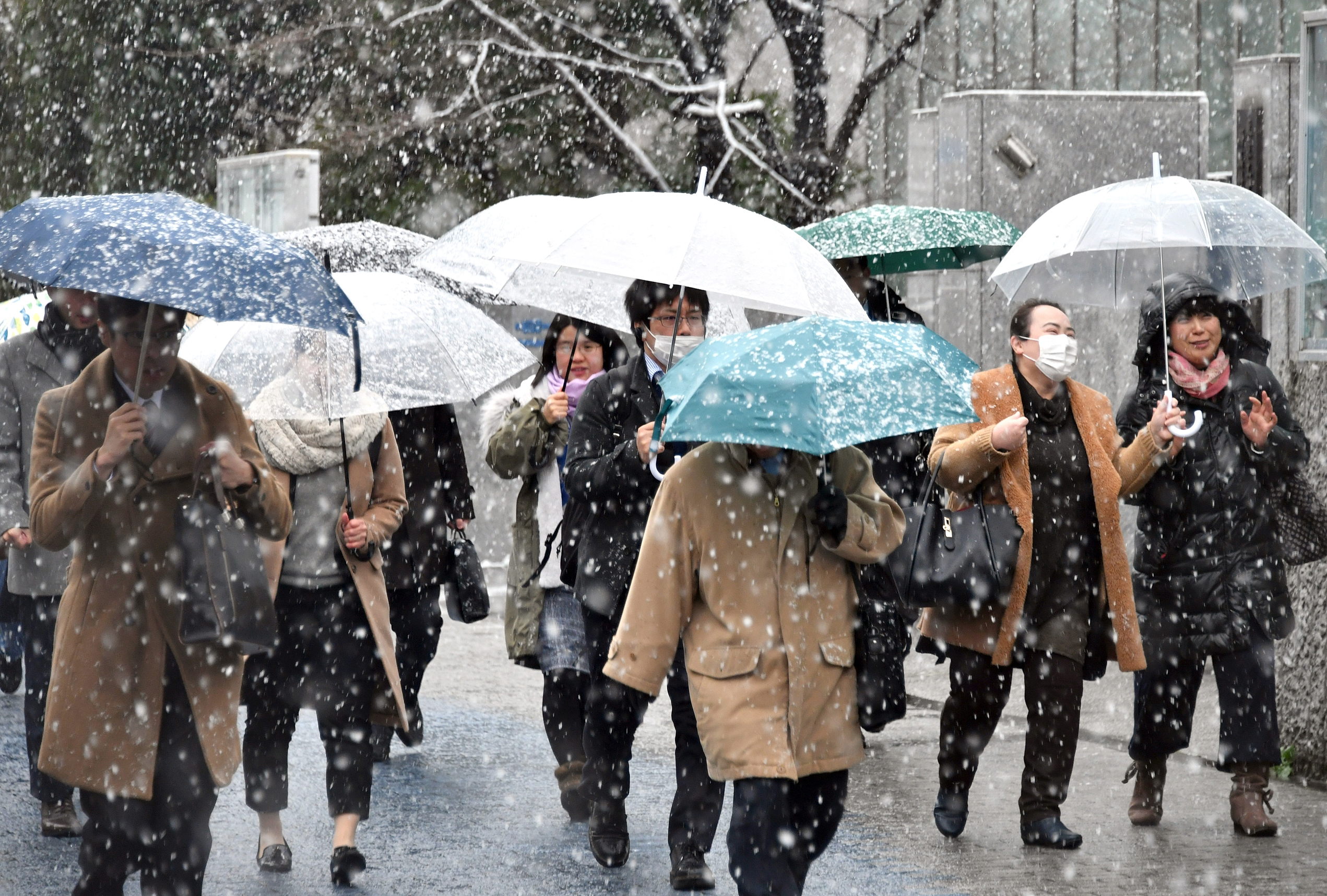 People walk in the snow in front of Tamachi Station in Tokyo on Monday.  | YOSHIAKI MIURA