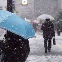 Pedestrians near Ryogoku Station in west Tokyo tromp through the snow on Monday. | CHISATO TANAKA