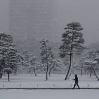 A man makes his way in the heavy snow at the Imperial Palace in Tokyo on Monday.  | REUTERS
