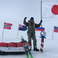 Adventurer Yasunaga Ogita holds up a Japanese flag at the South Pole Friday after walking 1,126 km alone — without extra supplies — from a coastal area of Antarctica, becoming the first Japanese to achieve the feat. | YASUNAGA OGITA