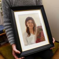 The husband of Rie Miyoshi, who was murdered by a stalker in 2012, holds her photograph in Kanagawa Prefecture last month. | KYODO