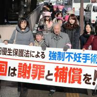 A group of lawyers holding a banner walk to the Sendai District Court on Tuesday, where they were representing a woman suing the government over her sterilization conducted under the now-defunct Eugenic Protection Law. | KYODO