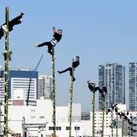 Members of the Edo Firemanship Preservation Association balance on top of bamboo ladders during a presentation in Tokyo on Saturday. Some 2,800 firefighters took part in the annual event.   AFP-JIJI
