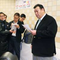 Stablemaster Kasugano, who also serves as communications chief for the Japan Sumo Association, fields questions from reporters at the Kokugikan in Tokyo in January. | KYODO