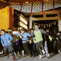 Runners in the annual 'Lucky Man Run' set off from the gate of Nishinomiya Shrine in Nishinomiya, Hyogo Prefecture, on Wednesday. The shrine has been holding the race for centuries and anoints the top three finishers as the year's lucky men or women. | KYODO