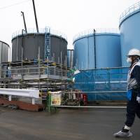 An employee walks past storage tanks for contaminated water at the Fukushima No. 1 nuclear power plant in Okuma, Fukushima Prefecture, operated by Tokyo Electric Power Company Holdings Inc., in February. | BLOOMBERG