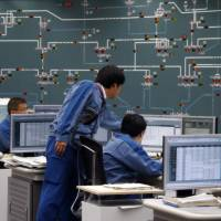 Tepco employees work at the company's central grid management center in Tokyo in this undated photo. The company is hunting both overseas and around Japan for startups and other investments with the potential to revolutionize the power sector. | BLOOMBERG