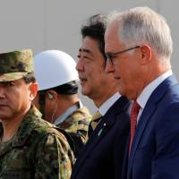 Prime Minister Shinzo Abe and Australian Prime Minister Malcolm Turnbull arrive at Narashino exercise field in Chiba Prefecture on Thursday.  | REUTERS