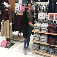 An Ethiopian employee works at Uniqlo's store in Tokyo's Kinshicho district in September. She is one of four refugees Uniqlo currently employs in Japan. | KYODO