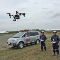 Officials from the Yaizu Crisis Management Division use a drone to locate a swimmer in need of help in the ocean as part of an emergency drill. | COURTESY OF YAIZU CITY CRISIS MANAGEMENT DIVISION